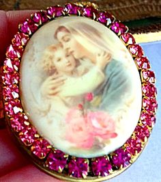 $79 Gorgeous porcelain cameo locket featuring the Blessed Mother Virgin mary holding the baby Jesus; Pink roses.  Pink and purple-pink rhinestones. Large gold plated bail. Good vintage condition.  Inside can hold 2 photo's or your personal prayer petition