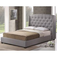 This Baxton Studio platform bed boasts grey linen upholstery and wooden construction. This modern bed also features a winged headboard with silver nail head trim and button tufting.