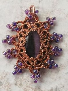 "Coppery      This pendent was tatted with two strands of copper sewing thread around a purple cats-eye.  The pendent measures 1"" X 1.25""."
