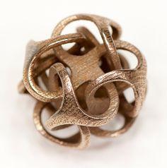 Geometric intertwining pendant in bronzed stainless steel.