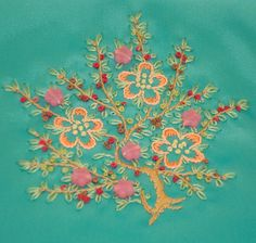 Flowering tree on blue green satin crazy quilt patch.