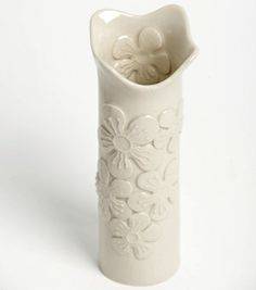 White ceramic vase with stylised Manuka flowers embossed onto the surface during the making process.  Measures approximately 19cm high and 6cm in diameter.