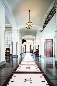 The front hall on the first floor features archways, columns, marble floors, and Tiffany-designed chandeliers. The sixty-foot runner on the floor was made in a saddle blanket design by King Ranch master weaver Emiliano Garcia.