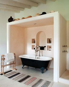 BRILLIANT way of partitioning within a large open space....I would even go so far as mirrors on both interior ends, metallic finish in niche, and simplistic linen curtains pulled back...with option to close while luxuriating in tub.  OH! and a few ledges for candles....LOTS of candles!