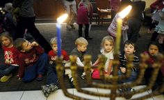 Students in the childcare program watch candles in the menorah burn after a celebration for the first day of Hanukkah at the York Jewish Community Center in York, Pa. on Dec. 16. ( Kate Penn/York Daily Record via Associated Press)