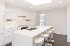 The bright, white eat-in kitchen features Leicht cabinetry, Miele appliances, and quartz countertops. White Kitchen Backsplash, White Kitchen Cabinets, Kitchen White, Apartment Kitchen, Kitchen Interior, Black Kitchens, Cool Kitchens, Layout Design, Modern Homes For Sale