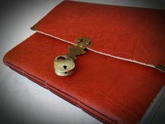 Caderno ou diário feito à mão com costura artesanal. <br>Couro sintético cor tijolo com fecho colonial e cadeado ouro velho.. <br>Modelo todo rústico, com as bordas desgastadas e o fecho e cadeado em estilo antigo. <br>Detalhe da cantoneira. <br>Forro de algodão mostarda, <br>- 100 FOLHAS RECICLADAS OU MARFIM SEM PAUTA.