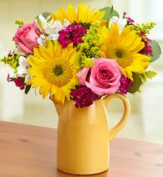 This vibrant bouquet is a perfect decoration for the kitchen table. The 'Sunbeam' sunflowers, white Peruvian lilies, and pink roses really brighten up the room. The flowers are kept in a multi-use pitcher which is a great decorative piece.
