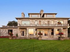 This massive estate in Vancouver has a stone facade, bay windows, dual chimneys, a large balcony, patio, stone urns, and manicured lawn.