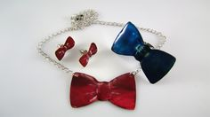 Bow, from Bowhouse  Handmade earrings, ring and necklace made of arzanto in the shape of a bow. The earrings (length: 2cm), the necklace and ring (length: 5cm) are hand painted in blue and fuchsia colour and coated with liquid glass.