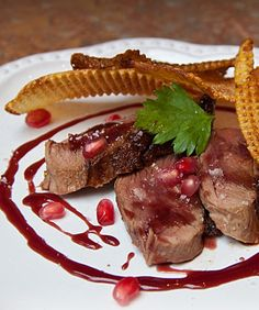 Duck breast with pomegranate reduction recipe  Ingredients include pomegranate juice, duck breasts, unsalted butter, fleur de sel, ground black pepper, fresh herbs