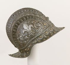 Italian Burgonet for the Farnese Guard, ca. 1545–47  This helmet is one of a series thought to have been made for the guard of Pier Luigi Farnese (1503–1547), who ruled as duke of Parma and Piacenza from 1545 to 1547. The raised fleur-de-lis on either side refers to the Farnese coat of arms (six blue fleurs-de-lis on a gold ground).