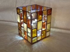 Handmade stained glass candle holder with different browns and gold textures and a glass bottom.. $58.00, via Etsy.