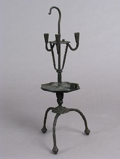 Candlestick 16th century, Spanish, Iron Met in NY Date: 16th century Culture: Spanish Medium: Iron Dimensions: Overall: 16 15/16 x 6 11/16 x 6 11/16 in. (43.1 x 17 x 17 cm) Classification: Metalwork-Iron Credit Line: Gift of Mrs. Ridgeley Hunt in the name of the late William Cruger Pell, 1907 Accession Number: 07.24.4
