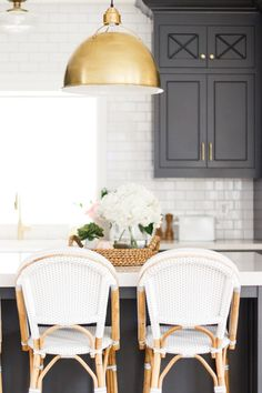 Black kitchen island with white countertops, gold pendant lights and white and ratan barstools | Salt Box Collective