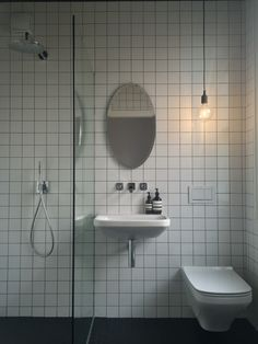 Finished wetroom ensuite bathroom. Fired earth tiles, Axor Citterio E taps, Duravit basin and toilet, Muuto light and Aesop toiletries. Fitted by SmarterHome4u, Manchester.