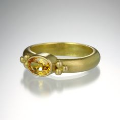 There is a sweet simplicity to this hand fabricated Reinstein/Ross 'Tania' ring.  Composed of the artists' custom alloyed 20K peach gold and an oval yellow sapphire with three gold side granules, this ring would make a great celebration ring for a graduation, birthday or anniversary! @QUADRUM