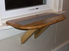 Perfect Purrch -Cat Window Perch. Size: approx 21 1/4long x 11 wide. It is made of Pine and CNC routed to allow a soft removable carpet to be inset in the center of the seat. Cats love to scratch and paw at the softness. Assembly is very easy. It attaches to the window sill with a Velcro