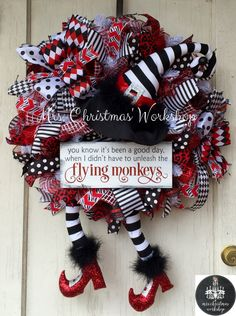 This is a Halloween wreath made with black, red and white premium deco mesh with matching ribbons and bows. The witch hat and legs are black and white with sparkly ruby red slippers or boots and black feathers. It features a sign that reads You know its been a good day when I didnt have to unleash the flying monkeys. How fun! This wreath inspired by the wicked witch in the Wizard of Oz. This wreath will need protection from the weather. Wreath measures 24H x 24W not including hat and boots…