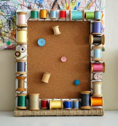 Spools of thread tied around a frame for a bulletin board - how adorable!