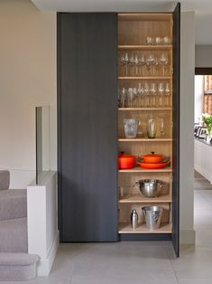 Glassware and cookware storage cupboard with dark stained oak exterior, natural oak interior.