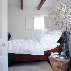 A neutral modern farmhouse bedroom featuring white walls and bedding, a wood sleigh bed and a natural wood tree stump bedside table - Contemporary Rustic Home Decor & Decorating Ideas