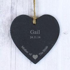 Personalise this Mother of the Bride Slate Hanging Heart with one line of 12 characters and one line of 20 characters. The design features a sweet heart motif at the bottom of the slate product, with the fixed text 'Mother of the Bride'. The heart has a piece of natural, rustic string which enables this item to be hung up.  PLEASE NOTE- Each slate piece will be unique as the item is cut by hand. Due to the nature of slate there will be some differences in the stone (such as texture, cut and…