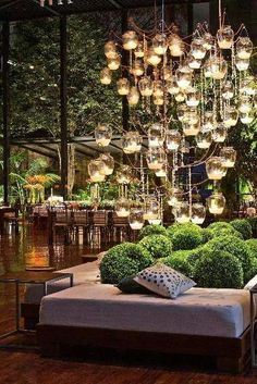Candle chandelier in lounge area of event.  Also love the cluster of shrubberies in between the benches. #modern #wedding