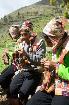 Peru: Three master knitters dressed in festival costume wear their naturally dyed alpaca chullos perched jauntily on the tops of their heads in a manner North Americans might think too small. The earflaps, some with buttons and beaded cords attached, act as a kind of counterbalance to keep them on.