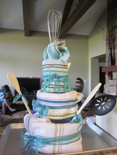 tea towel cake with cooking accessories! This would be cool gift or benefit auction idea
