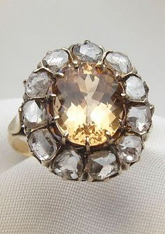 A handmade Victorian ring centered with a 3.34 carat oval, brilliant golden topaz surrounded by rose-cut diamonds. Online at Isadoras.com.