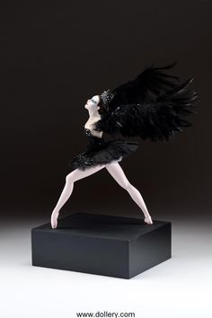 "Vickie Arentz - ""Black Swan"" It's a 17"" (43cm) tall figure on a 4"" (10cm) tall base making the entire piece 21"" (53cm) tall by 20"" (51cm) wide. Polymer clay figure sculpted in one piece with detachable real feather wings. Hand painted eyes, viscous fiber wig, costume of leather, cotton voile and silk with hand beaded details and Swarovski crystals."