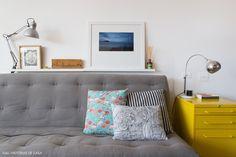 Sala de estar compacta tem sofá estilo futon e porta arquivos como mesa lateral.