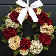 This beautiful holiday wreath is loaded with faux hydrangeas, peonies and dahlias in deep red and cream, a gorgeous addition to your front door for the Valentine's Day and Christmas holidays. The wreath is finished off with a mix of artificial leaves and a bow in your choice of color. Your wreath will be handmade to order. (Bow placement may vary.)