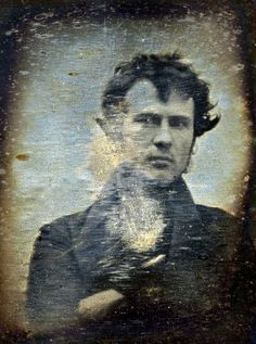 This is one of the earliest known photographs of a human. A self portrait taken in 1839, it shows a young Robert Cornelius (1809-1893) standing outside his family's lamp-making shop in Philadelphia. Cornelius was an American of Dutch descent whose knowledge of metallurgical chemistry was to help in perfecting the process of silver-plating, then employed in the production of daguerreotypes