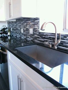 Black countertop, this backsplash, grey cabinets, with painted areas of walls in coral!