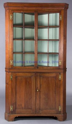 """CAROLINA CHIPPENDALE WALNUT CORNER CUPBOARD,  one-piece construction, canted returns, the upper section with molded cornice over two hinged eight-light doors above molded waist, the lower section with two hinged fielded-panel doors over cut-out bracket-foot base with full height. Yellow pine secondary wood. Retains possibly original brass H hinges and a fine old surface with rich color.  Fourth quarter 18th century. 89 1/2"""" H, 31"""" corner. <BR><I>Good overall condition with minor area of rest... Southern Furniture, North Carolina Furniture, Colonial Furniture, Primitive Furniture, Country Furniture, Antique Furniture, Painted Furniture, Corner Cabinet Dining Room, Corner China Cabinets"""