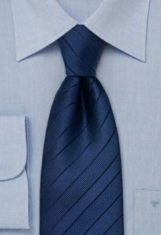 Elegante corbata azul oscuro con rayas finas negras. La corbata está hecha a mano.El relleno elástico de la corbata permite que ésta retome su forma original despues de usarla.