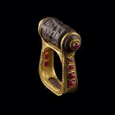 Золотое кольцо с рубинами. Кольцо датируется приблизительно 3500 г до н. э. Цилиндр, закреплённый на золотой основе, использовался для оттиска необходимых письменных знаков на поверхности