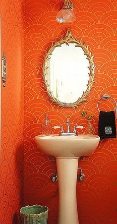 small bathroom with gold and orange wallpaper, round gold mirror, pedestal sink... Beautiful Bathroom Inspiration: Orange Bathrooms from The Bathroom Bliss Blog by Rotator Rod, the original curved shower rod that rotates!