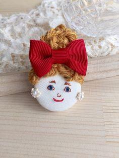 女の子の顔刺繍をしたヘアゴムです。 娘の髪にお人形がついていたらかわいいかな…と思い作り始めたお品です。ヘアゴムとしてはもちろん、結びつけてバッグチャームや帯留めなどにも。  くるみボタンベースになっています。 素材  コットン、アクリル毛糸、ビーズ、レ...