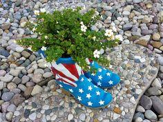 Dieses Paar Stiefel bunt bemalt mit eine amerikanische Flagge stehend als Pflanzer in weiß gefärbt Blumen, ist ein Anblick in einem Meer aus Kies und Steinen.