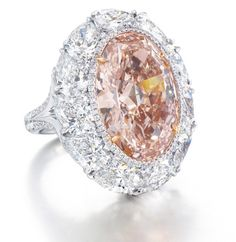 A RARE COLOURED DIAMOND AND DIAMOND RING  Centering upon an oval-shaped fancy intense orangy pink diamond weighing approximately 12.85 carats, within a brilliant-cut diamond border and pear-shaped diamond surround, joined to the brilliant-cut diamond bifurcated half-hoop, mounted in platinum and 18k rose gold.
