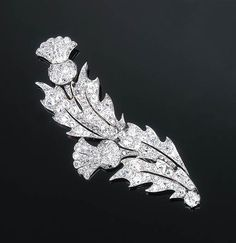 A Diamond Thistle Brooch   Of slightly scrolled openwork design, each stylised thistle set throughout with old-cut diamonds, circa 1910, one small diamond deficient, 8.0 cm long