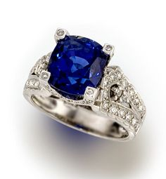 A sapphire and diamond ring  centering a cushion-shaped sapphire, weighing 6.75 carats, within an intricate mounting of round brilliant-cut diamonds; mounted in eighteen karat white gold
