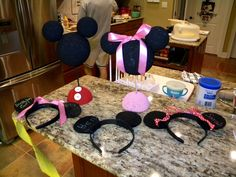 We did a mickey mouse clubhouse birthday party.  I made all the kids mickey ears w/ their names in glitter glue on the ears plus a red bow for the girls.  The birthday girl had a pink bow.  Just used black headbands which I painted because I couldnt find enough black headbands.  Cut the ears out of felt (from a template from the MMCH website) folded in half and hot glue them together on to the band.  I painted some styrofoam balls for the mickey and minnie head centerpieces.