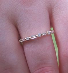A fabulous stacker ring or wedding band this ring is simple, elegant, and full of radiant sparkle. .3 carats of full cut alternating round and baguette shape diamonds form the top of this half eternity band. Each stone is delicately set between two prongs and nestled in the gold below for