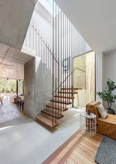 CO-AP has renovated and extended a typical suburban home in Australia, adding a two-storey concrete structure that opens onto a garden at the rear.