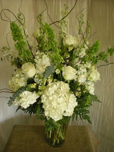 Bells of Ireland - nice way to add height to arrangement.  Would want to incorporate with blush / creams of peonies and hydrangeas