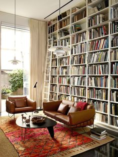 Home library nirvana: Floor to ceiling shelves, #Noguchi coffee table and #LouisPoulsen floor lamp.